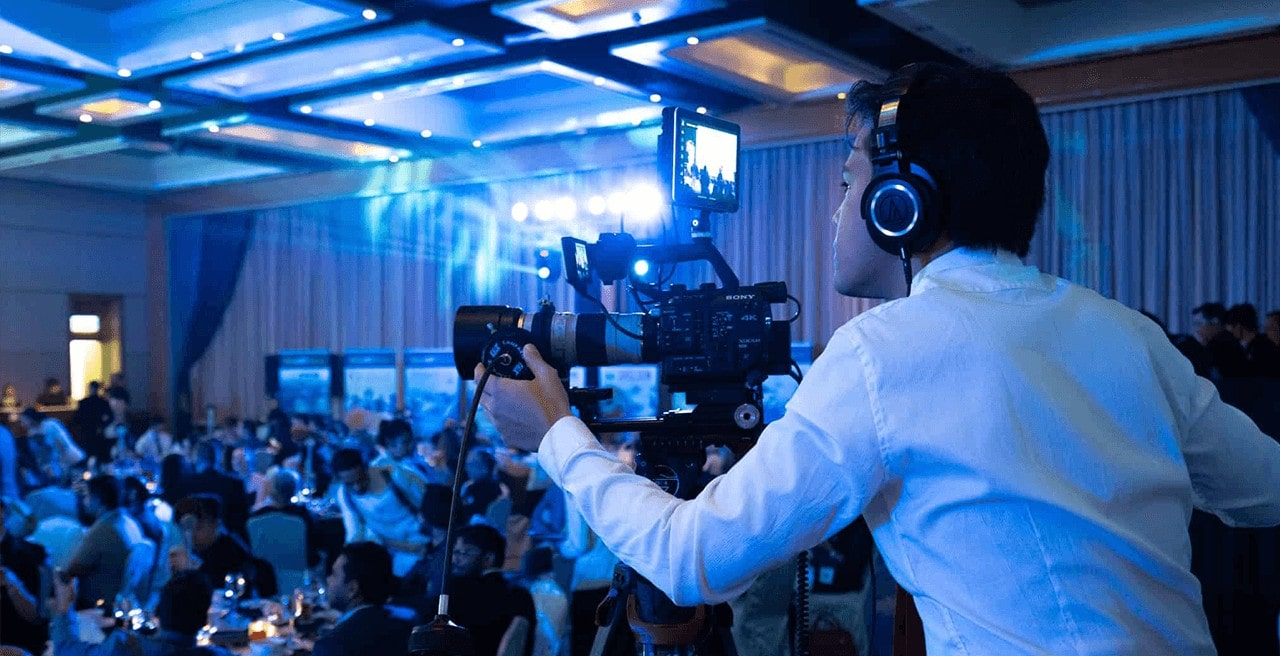 Videographer using Sony FS5 video camera to film a conference